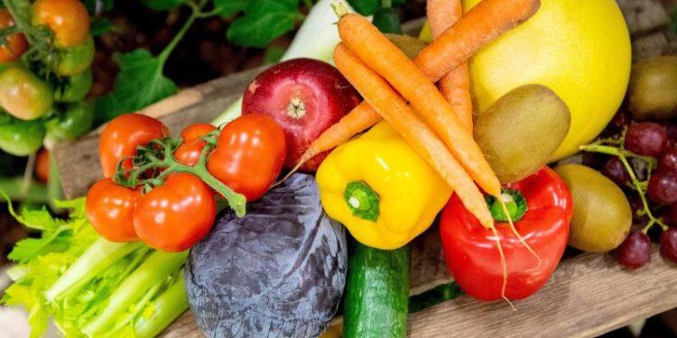 Verschiedene Obst- und Gemüsesorten auf einem Holzbrett.