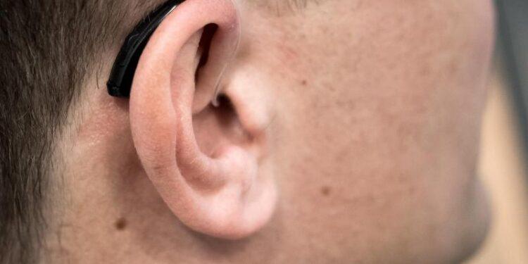 Ein Hörgerät hinter dem Ohr eines Mannes.