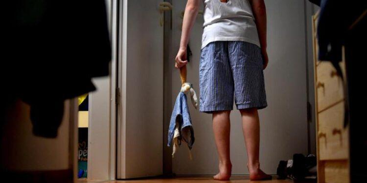 Ein Kind steht in einem Hausflur.