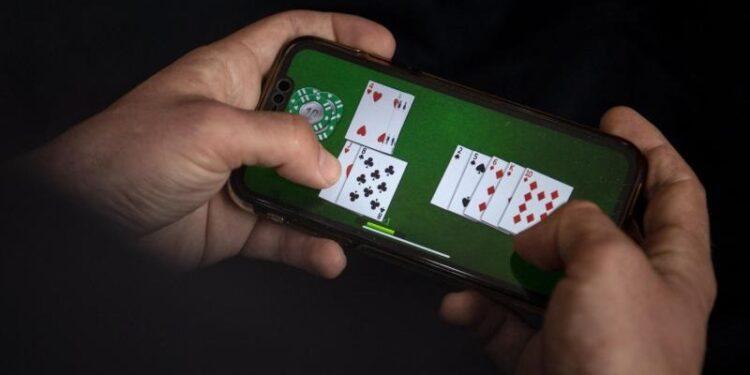 Eine Person spielt ein Kartenspiel auf dem Smartphone.