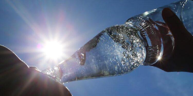 Eine Person trinkt Wasser aus einer Flasche.