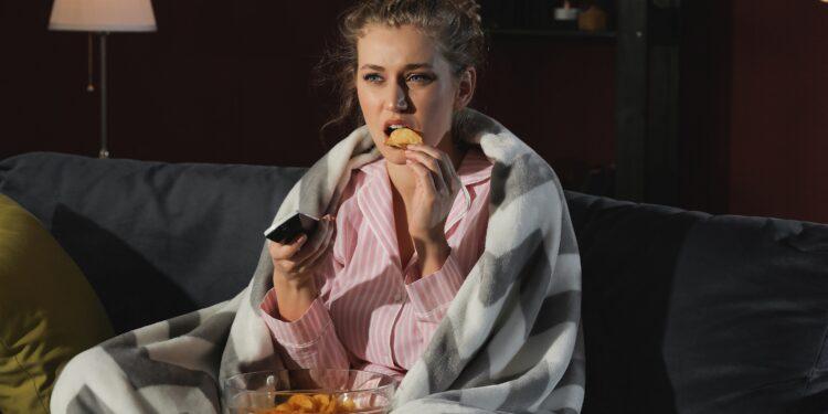 Frau isst Chips vorm Fernseher.