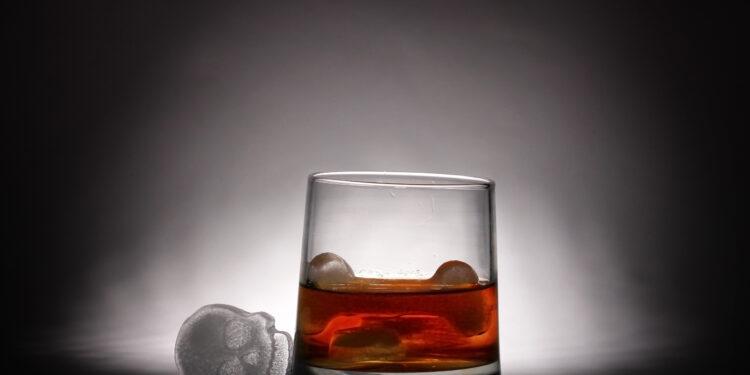 Bild von einem Glas Alkohol mit einen Totenkopf aus Eis daneben.