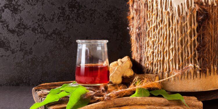 Ein roter Tee steht umgeben von natürlichen Zutaten auf einer schwarzen Oberfläche.