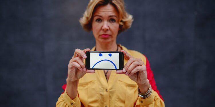 Blonde Frau zeigt Handy mit traurigem Gesicht.