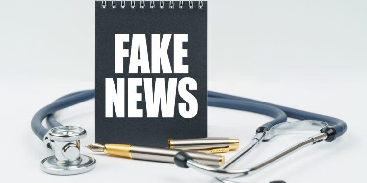 """Auf einem Schreibblock steht """"Fake News"""", daneben liegt ein Stetoskop."""