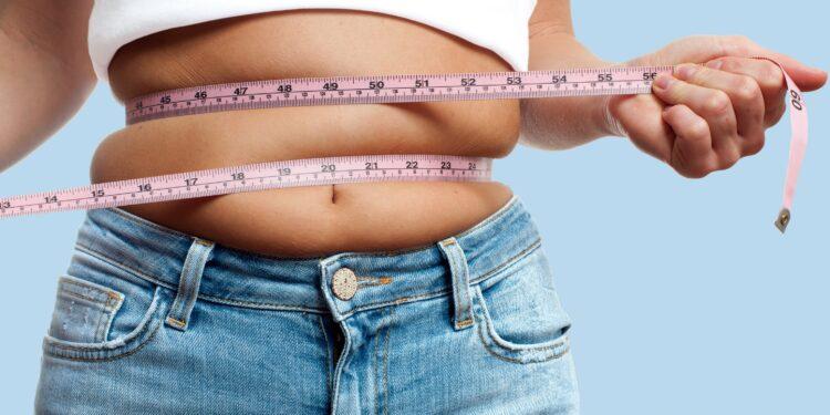 Übergewichtige Frau mit Maßband um ihren Bauch