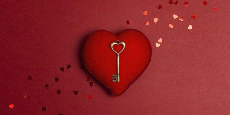 Ein kupferner Schlüssel liegt auf einem roten Herz.