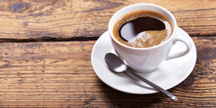 Eine Tasse schwarzer Kaffee mit einem Löffel auf einem Holztisch
