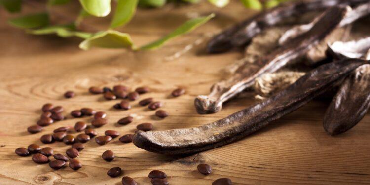 Getrocknete Karob-Schoten und Samen liegen auf einer hölzernen Oberfläche.
