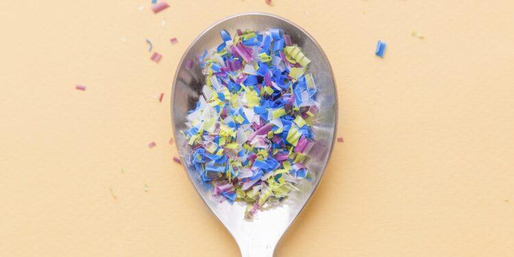 Ein Löffel ist gefüllt mit winzigen Plastikpartikeln.