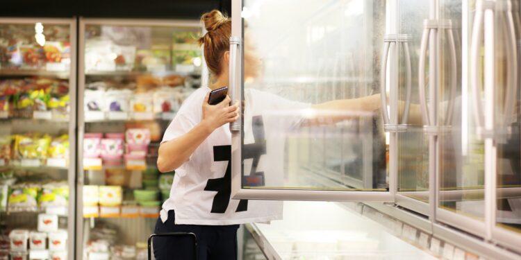 Frau wählt Tiefkühlkost aus einem Supermarkt-Gefrierschrank