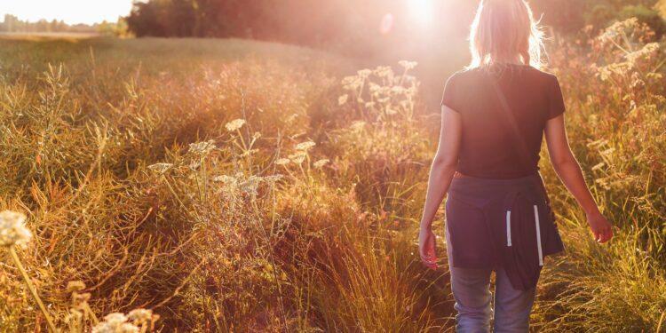 Eine Frau geht an einem Feld spazieren.