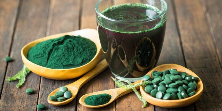 Dunkelgrüner Extrakt aus der Spirulina-Alge als Getränk, Pulver und Kapseln auf Holztisch