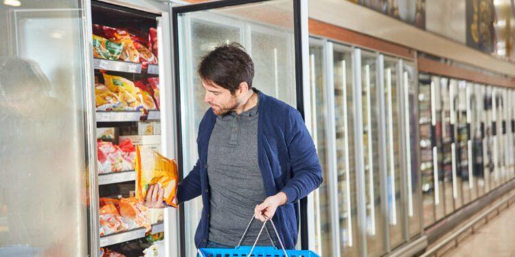 Ein Mann begutachtet ein Tiefkühlprodukt im Supermarkt.