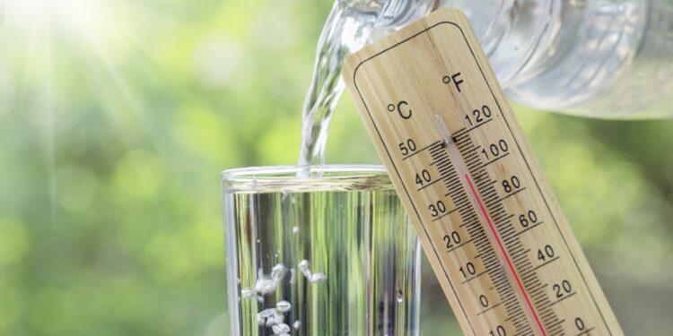 Ein Thermometer vor einem Glas in das Wasser geschüttet wird