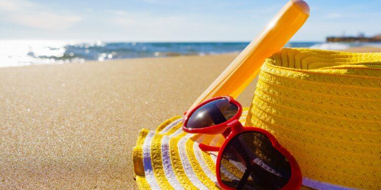Ein Hut, eine Sonnenbrille und Sonnencreme liegen auf einem Strand.