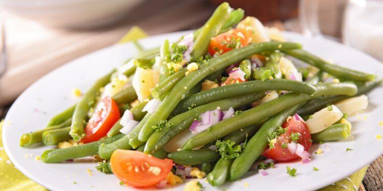 Bunter Salat mit grünen Bohnen auf weißem Teller