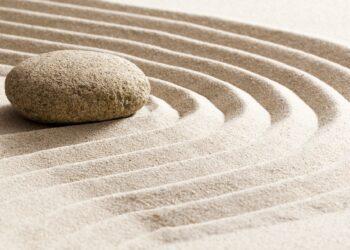 Ein Stein liegt im Sand.
