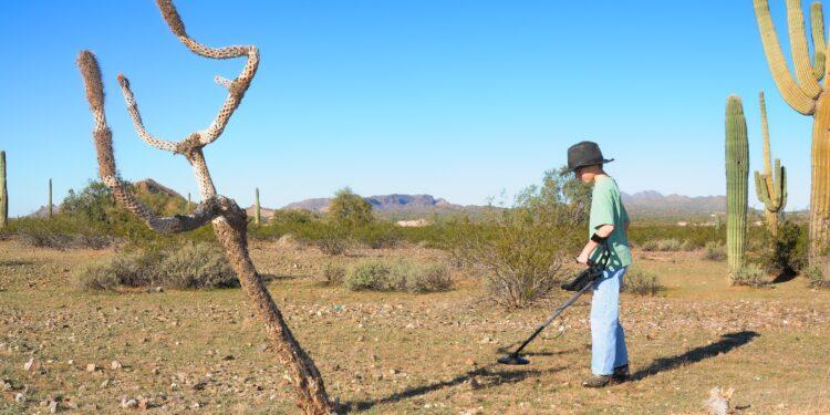 Un ragazzo cerca nel deserto con un metal detector.