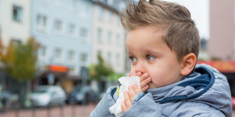 Un ragazzo si soffia il naso.