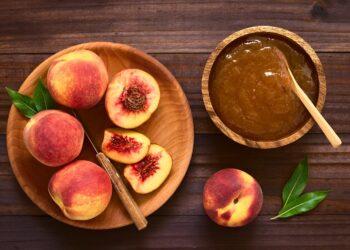 Frische reife Pfirsiche auf Holzteller und Pfirsichmarmelade in Holzschüssel