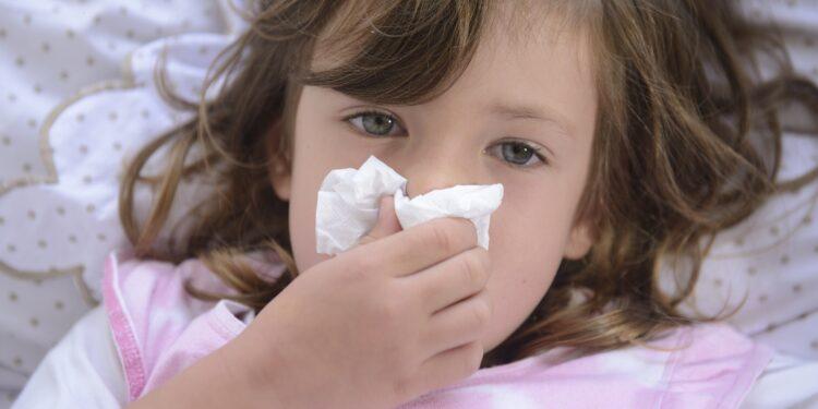 Kleines, im Bett liegendes Kind schneuzt in ein Taschentuch