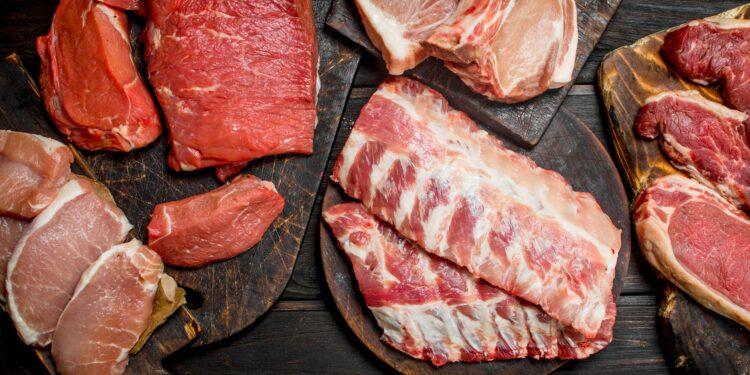 Verschiedene Sorten von rotem Fleisch liegen auf einer hölzernen Oberfläche.