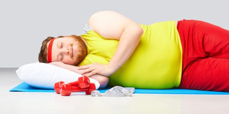 Ein Mann mit Übergewicht liegt auf einer Fitness-Matte und schläft.