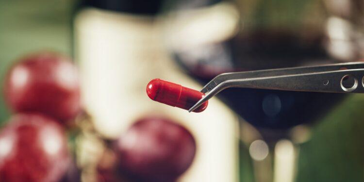 Kapsel mit Resveratrol sowie roten Weintrauben und Weinflasche im Hintergrund.