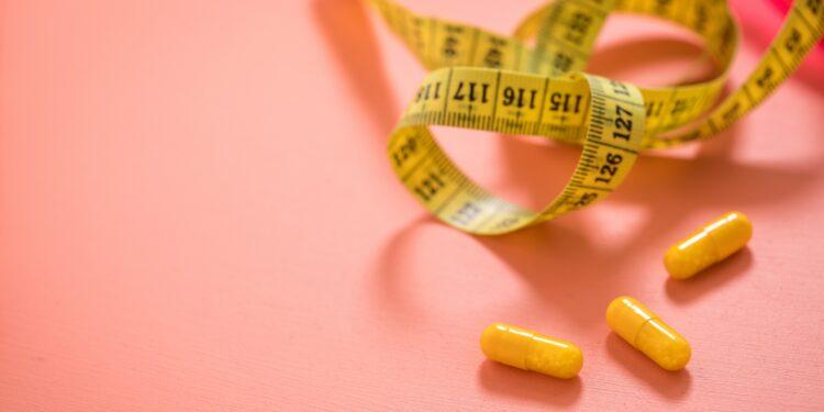 Einige Pillen und ein Maßband liegen auf einer rosa Oberfläche.