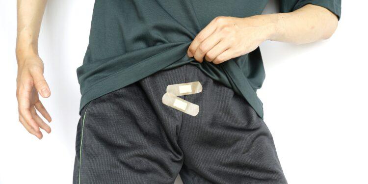 Ein Mann hat zwei Pflaster auf den Reißverschluss seiner Hose geklebt.
