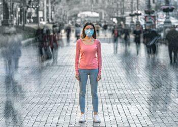 Junge Frau mit medizinischer Maske steht allein im Freien