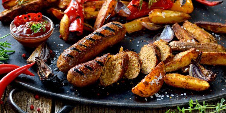 Vegane Bratwust vom Grill mit scharfer Sauce und Kartoffelspalten
