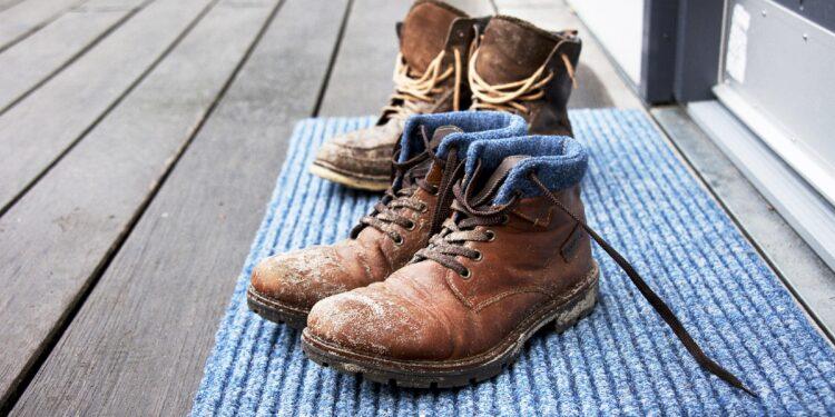 Schmutzige Stiefel stehen auf einem Fußabtreter.